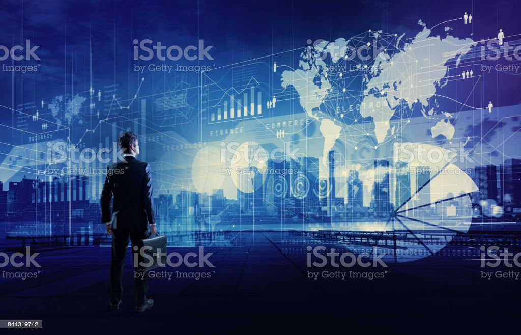 standing businessman who looks various graphics of business. Internet of Things. Information Communication Technology. Digital transformation. Abstract mixed media. stock photo