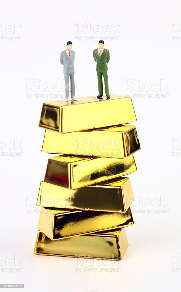 Standing businessmans on gold ingots stock photo