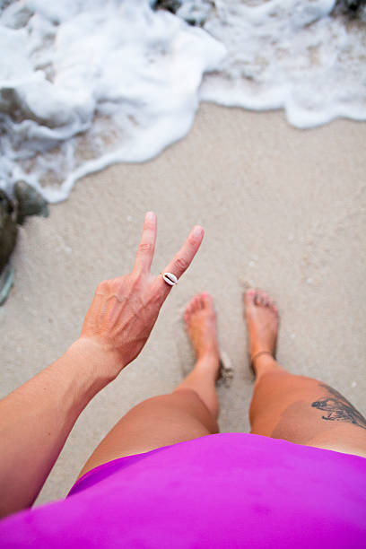 standing by the sea peace sign - shell tattoos stock-fotos und bilder