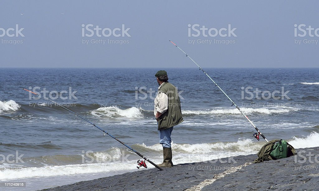 Standing fisherman with two rods, fishing in the sea stock photo
