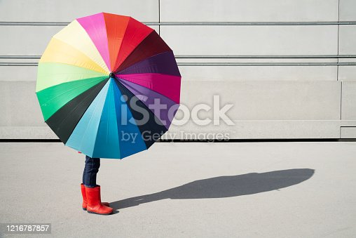 Standing girl with multicolored umbrella in front of a concrete wall