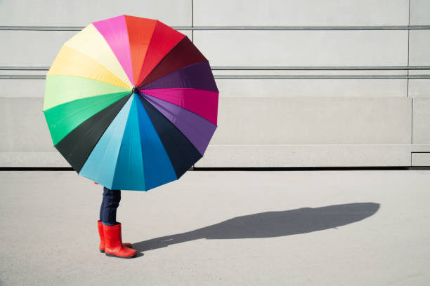 Standing girl with multicolored umbrella in front of a concrete wall stock photo