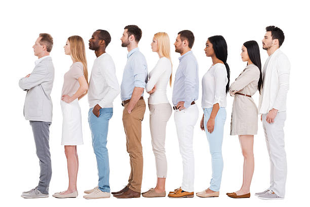 Standing in a row. Full length of confident multi-ethnic group of people in smart casual wear looking away while standing in a row and against white background people in a row stock pictures, royalty-free photos & images