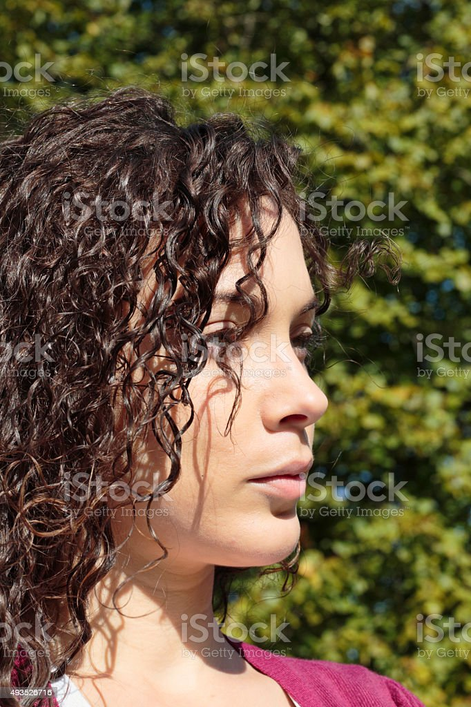 Profile face curly-haired beautiful shapely Canadian outdoor girl stock photo