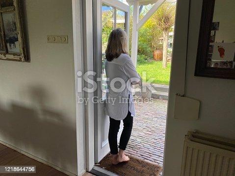 Woman standing in door too keep distance in Corona times