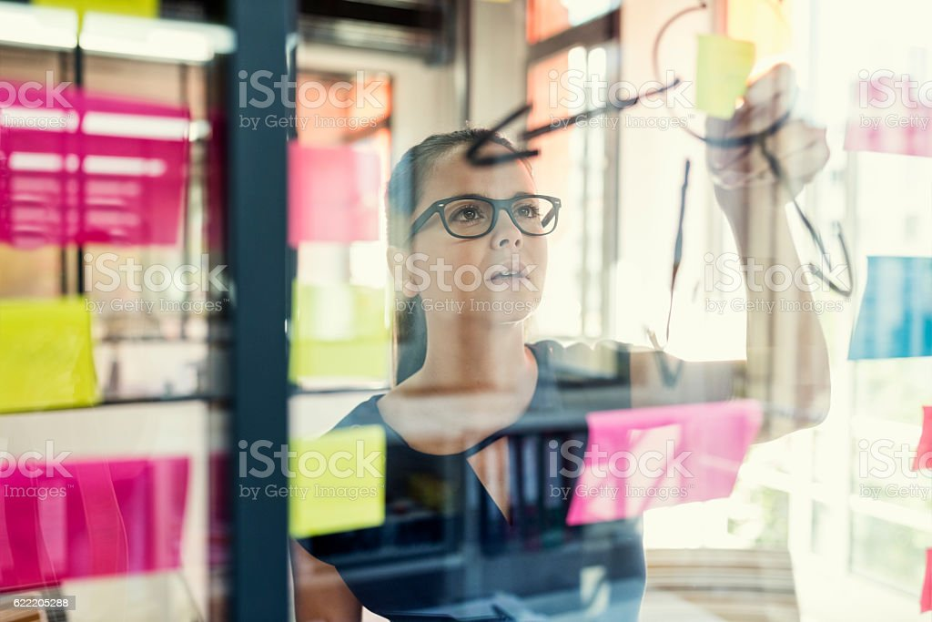 Standing in front of glass wall young female with stickers royalty-free stock photo