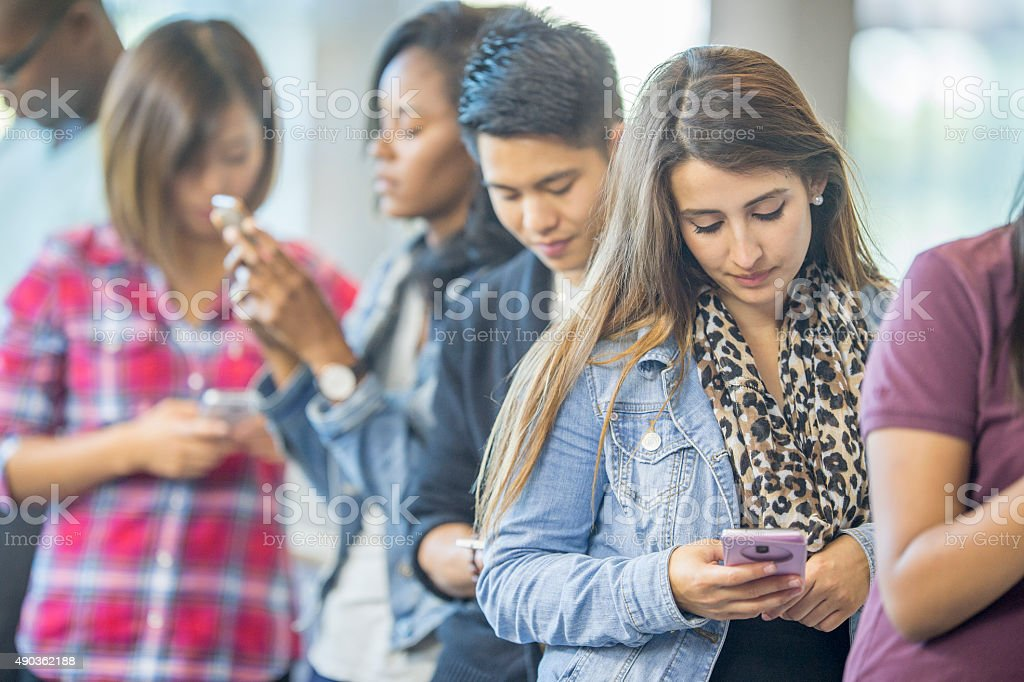 Standing in Line Texting stock photo