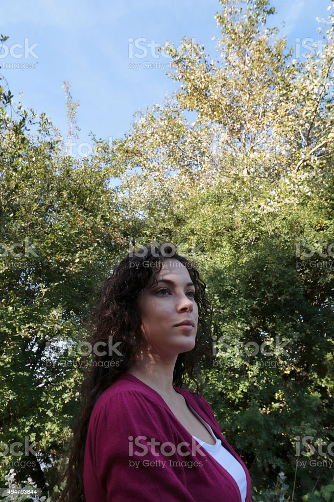 Shaded face low viewpoint curly-haired beautiful Canadian outdoor girl stock photo