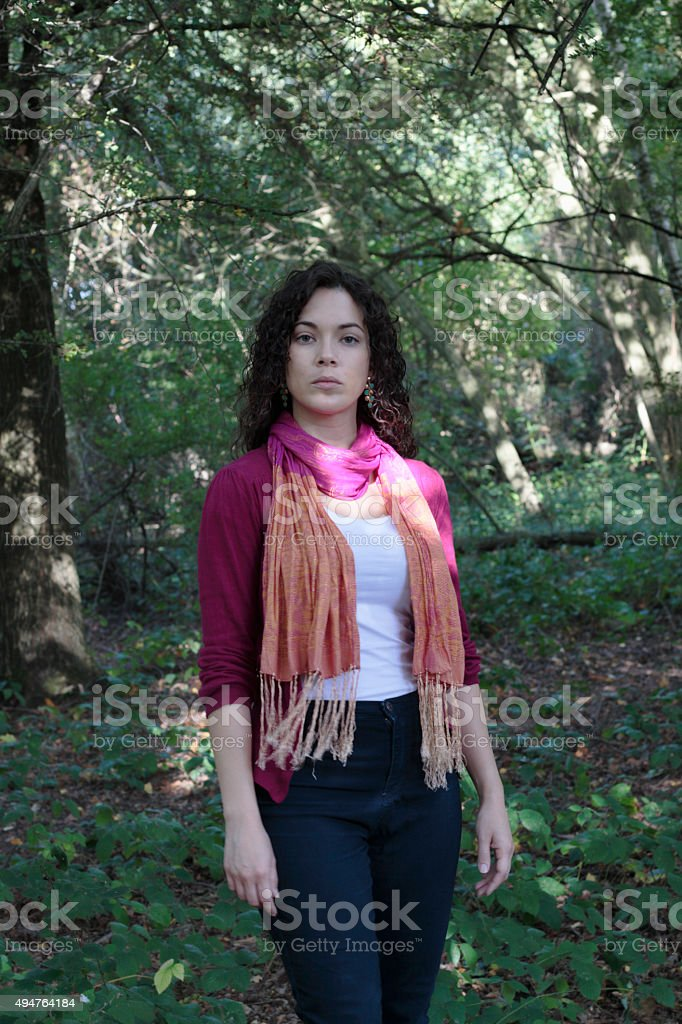 Curly-haired beautiful Canadian outdoor girl in shady woodland stock photo