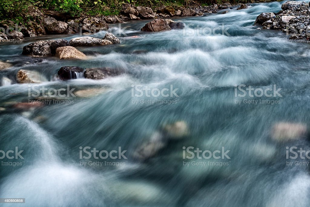 standing in the middle of a flowing water riverbed stock photo