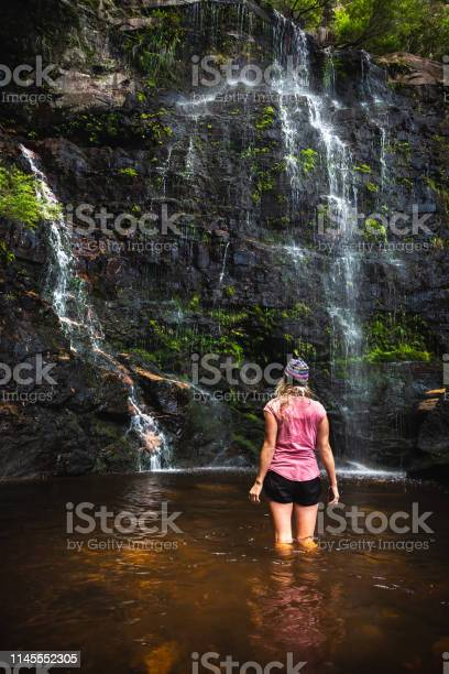 Photo of Standing in the rock pool at the bottom of the falls deep down in the mountain valley