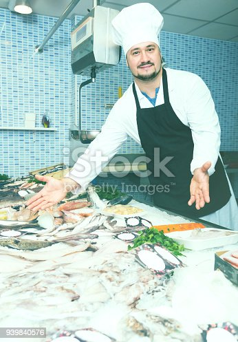 istock Standing laughing man shows the fish counter 939840576