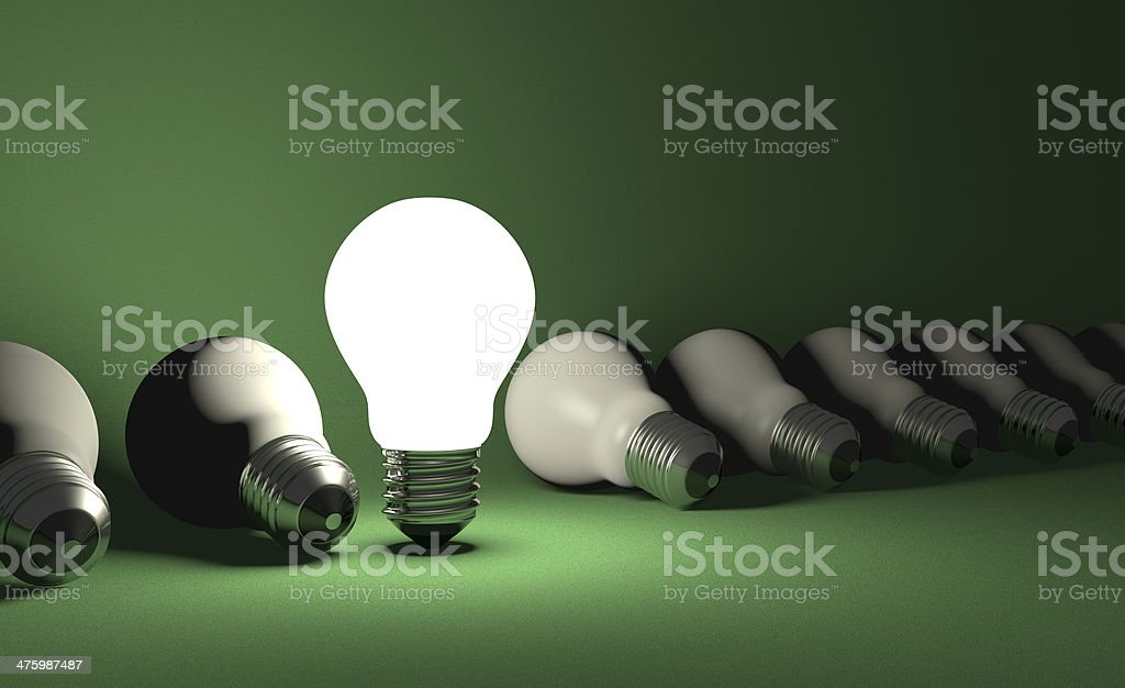 Standing light bulb in row of lying ones on green stock photo