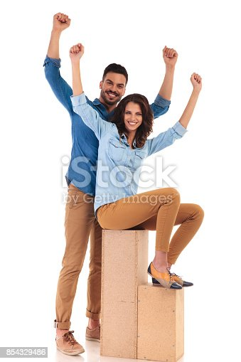 854381886 istock photo standing man and seated casual woman celebrating success 854329486