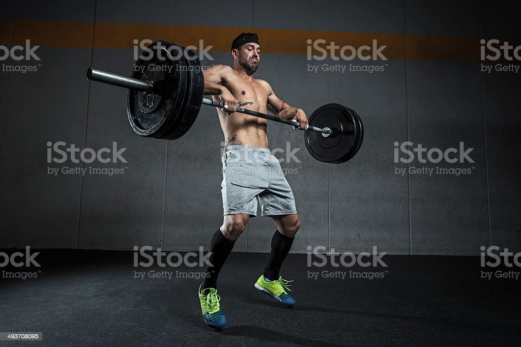 Standing man lifting weight stock photo