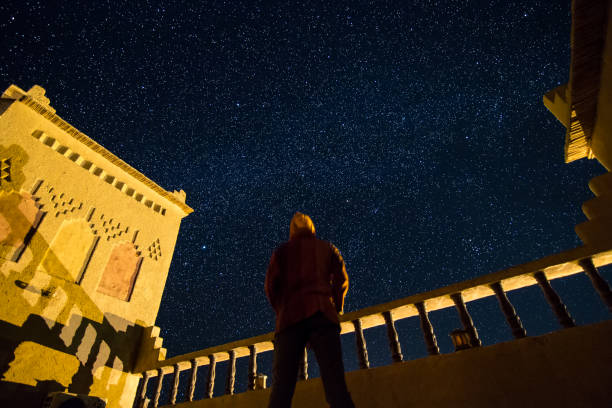 A standing man looking at the starry sky on the roof of a kasbah in southern Morocco. stock photo