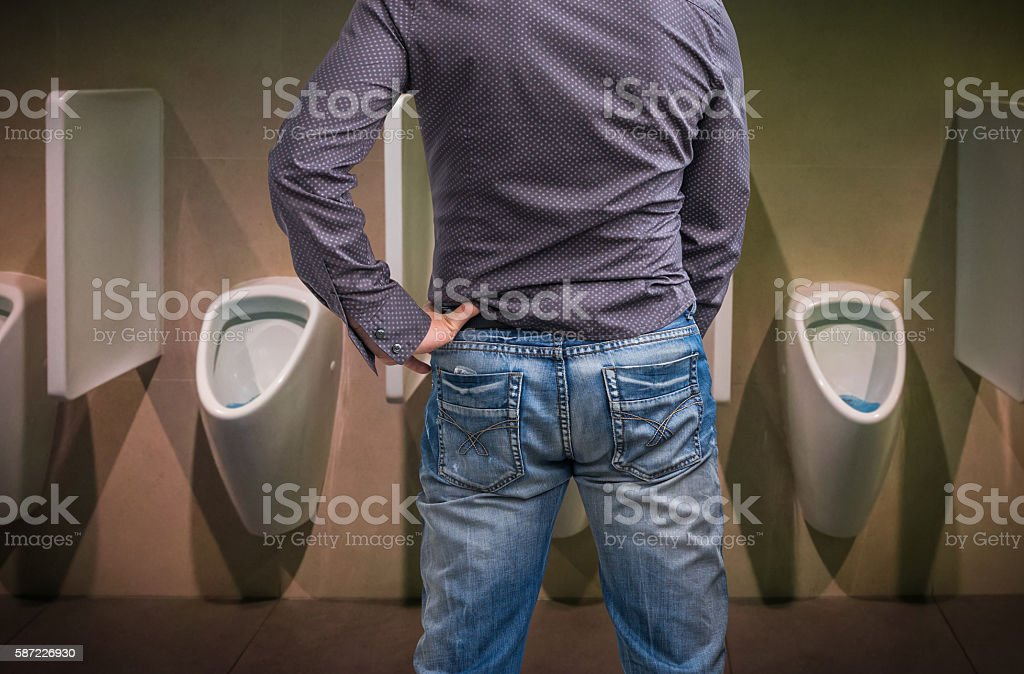 Standing man peeing to a urinal in restroom stock photo
