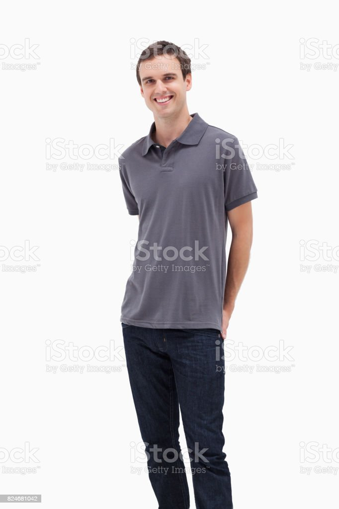 Standing man smiling with his hands behind his back stock photo