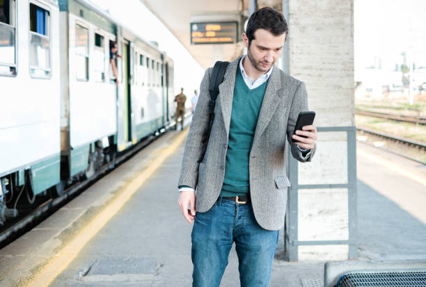 standing man waiting for the train in a train station platform - foto stock
