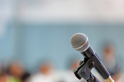 istock Standing microphone for speaker's speech in the seminar room with audience in the background 1060699320