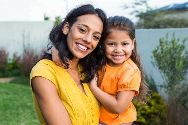Standing mother holding her daughter outdoors stock photo