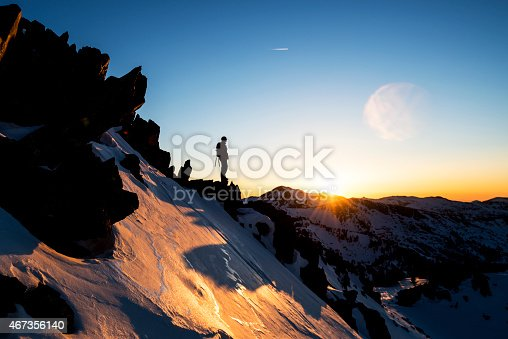 Strong mountain climber near the summit watching the sunset from the edge of a cliff