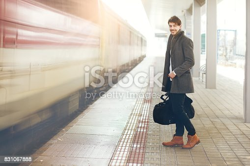 handsome young man with travel bag standing on railway platform outdoor, retro toned image