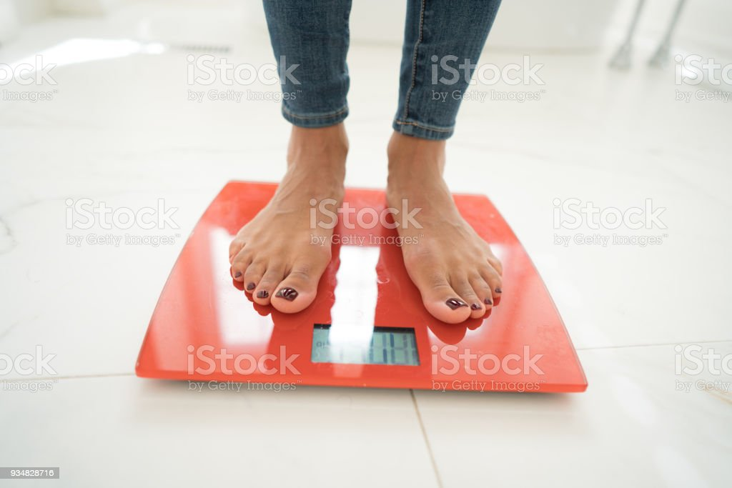 Standing on scales stock photo