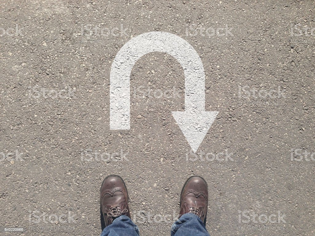 standing on the asphalt concrete floor in front of u turn symbol stock photo