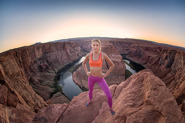 Standing on the Edge - Horseshoe Bend A woman in sport clothes standing right on the edge 1000 feet above the Colorado River of the Horseshoe Bend. Extreme Wide Angle shot. Nikon D810. horseshoe bend colorado river stock pictures, royalty-free photos & images