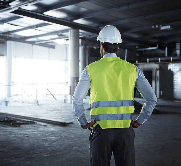 Standing on the edge of engineering Cropped shot of an engineer on a construction site reflective clothing stock pictures, royalty-free photos & images