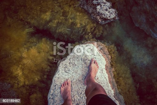 High angle view of male barefoot. Standing on the rock,