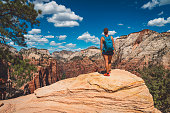 People on hiking trip in the mountains walking on pathway. Zion National Park, Utah, USA