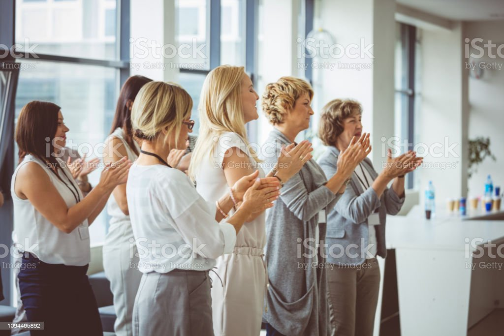 Standing ovation to the speaker Group of female professional standing and applauding after a speech by speaker. Group of women clapping during training session in conference hall. Adult Stock Photo