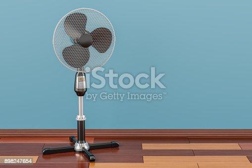 istock Standing pedestal electric fan in room on the wooden floor, 3D rendering 898247654