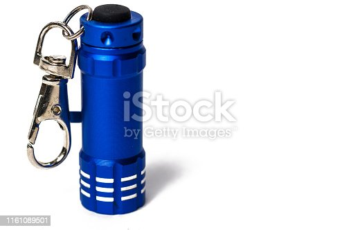 Standing Small metallic blue flashlight key chain on white paper background