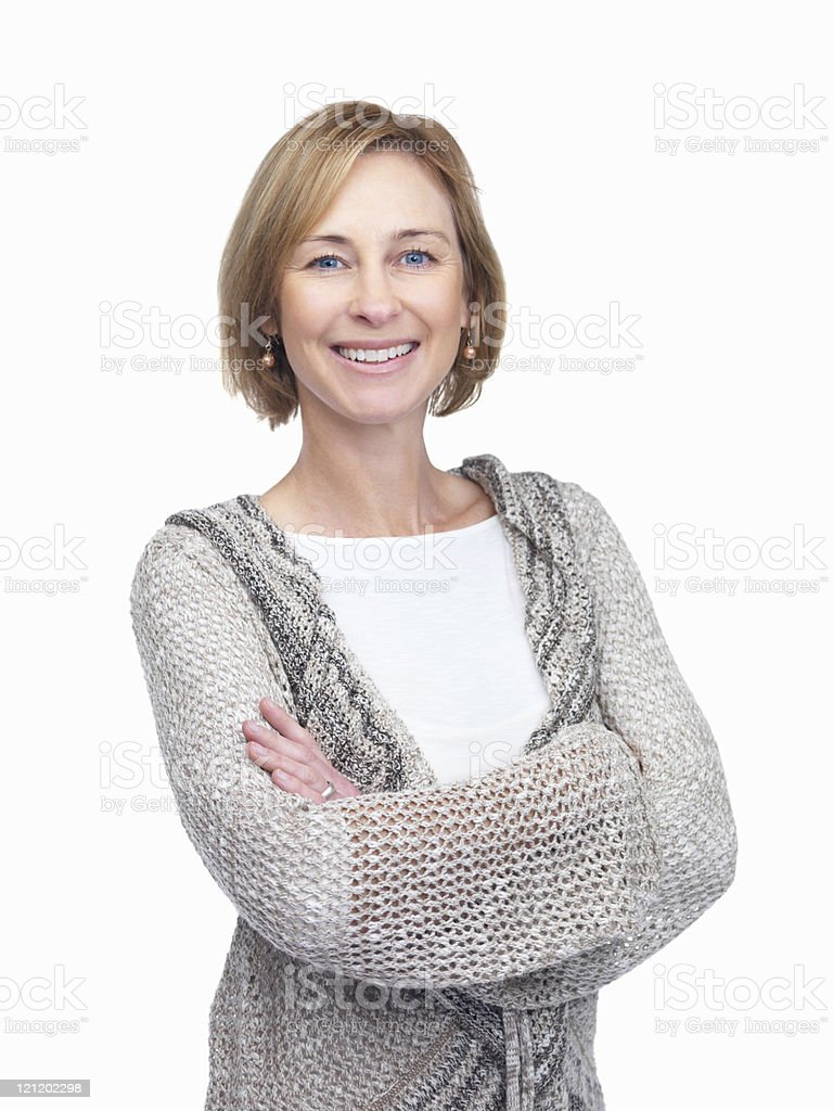 A standing, smiling mature woman with arms folded stock photo