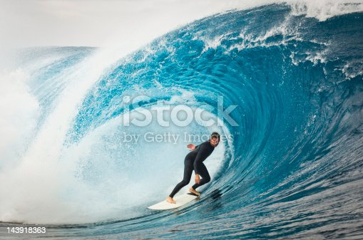 A male surfer cruising along a huge wave.