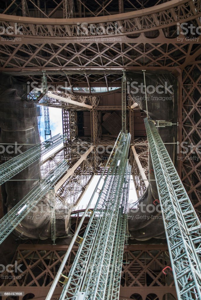 Standing under Eiffel Tower Tour Eiffel blue sky clouds stock photo