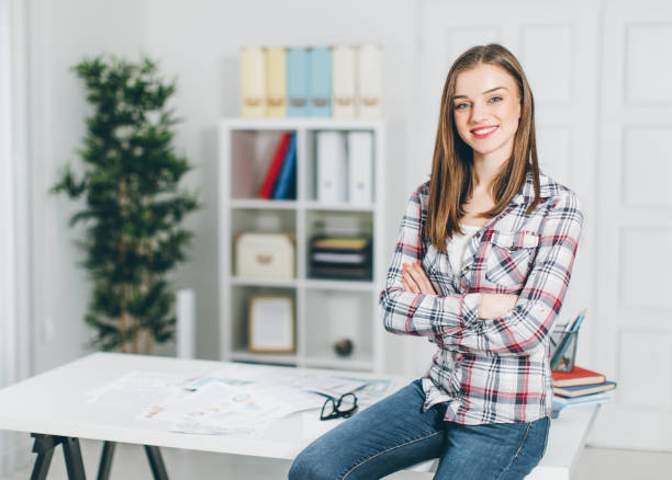 Standing woman in front of desk stock photo