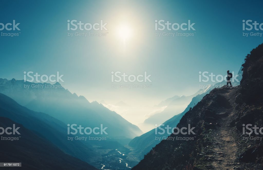 Standing woman on the hill against mountain valley at bright sunny day. Landscape with girl, trail, mountain, blue sky with sun and low clouds at sunset in Nepal.  Lifestyle, travel. Trekking stock photo