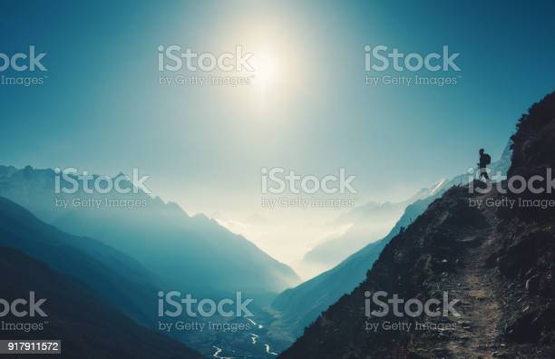 Photo of Standing woman on the hill against mountain valley at bright sunny day. Landscape with girl, trail, mountain, blue sky with sun and low clouds at sunset in Nepal.  Lifestyle, travel. Trekking