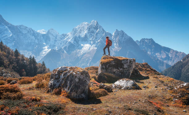 Standing woman with backpack on the stone and beautiful mountains at sunset. Landscape with sporty girl, high rocks, snowy peaks, blue sky in autumn. Travel in Nepal. Lifestyle. Trekking in Himalayas stock photo