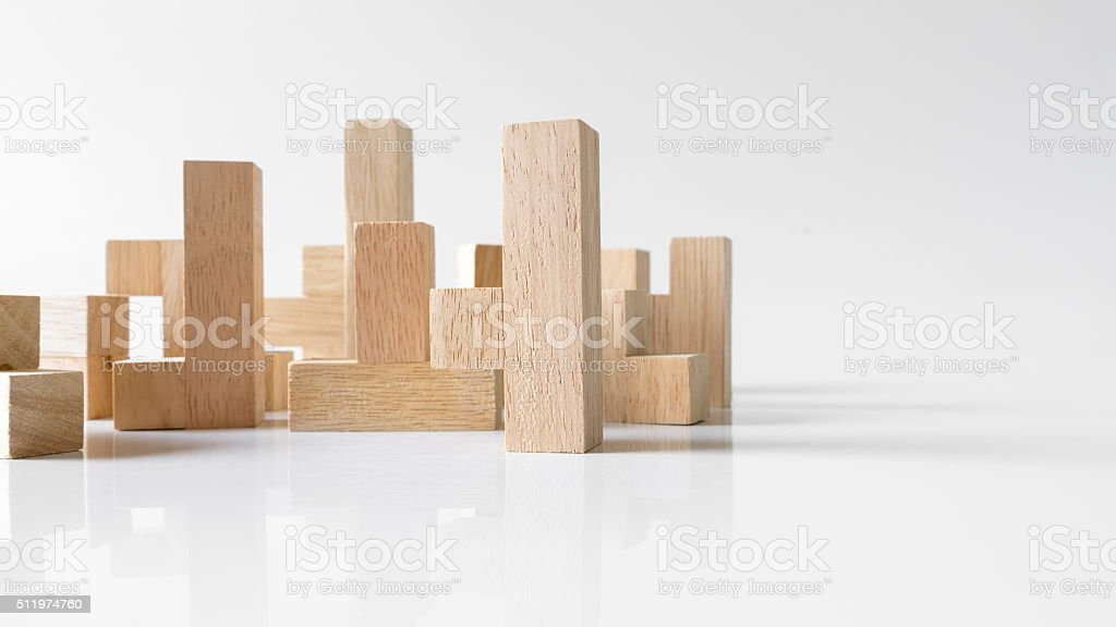 Standing wooden block puzzle of various shapes on empty background stock photo