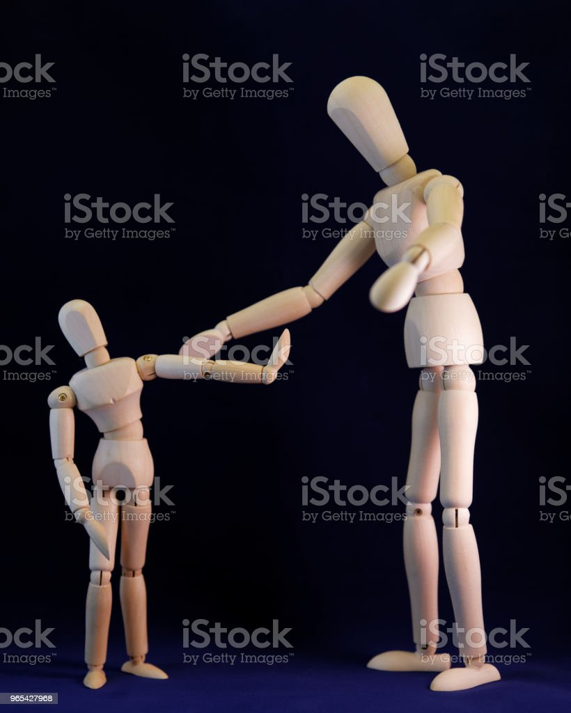 2 standing wooden mannequins, larger inviting a smaller one, which is refusing zbiór zdjęć royalty-free