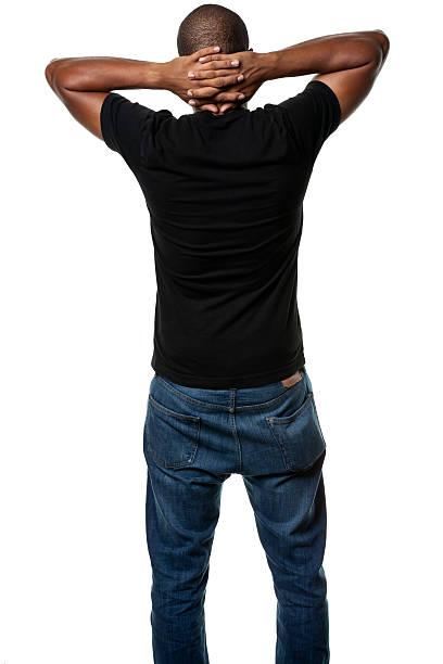 giovane uomo in piedi con le mani intrecciate dietro la testa, vista posteriore - mani dietro la testa foto e immagini stock
