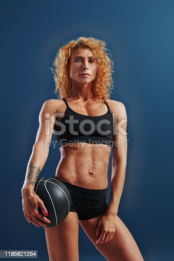 676005390istockphoto Stands with black soccer ball. Redhead female bodybuilder is in the studio on blue background 1185621254