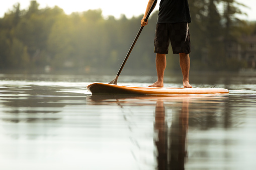 SUP Stand-up Paddleboard. Close-up on legs of a man paddleboarding