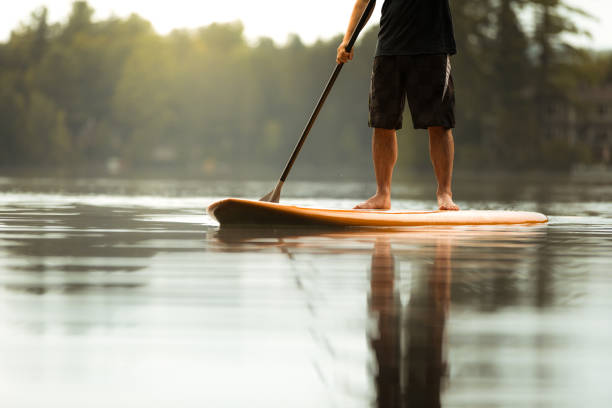 SUP Stand-up Paddleboard. Close-up on legs of a man paddleboarding stock photo