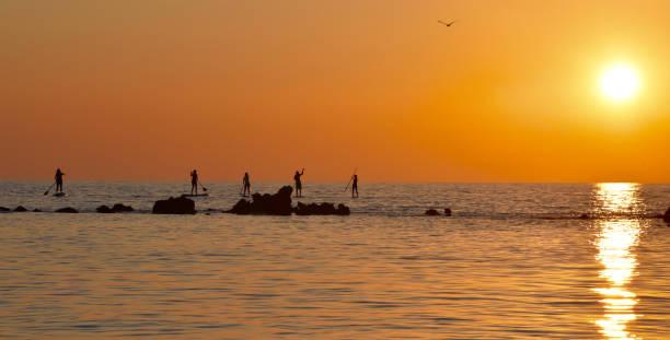 Stand-up Paddlers Sunset Corfu, Greece stock photo